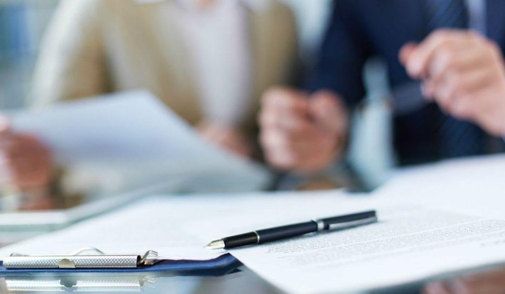 Como dar baixa na carteira de trabalho da empregada domestica - contratos e canetas sobre a mesa