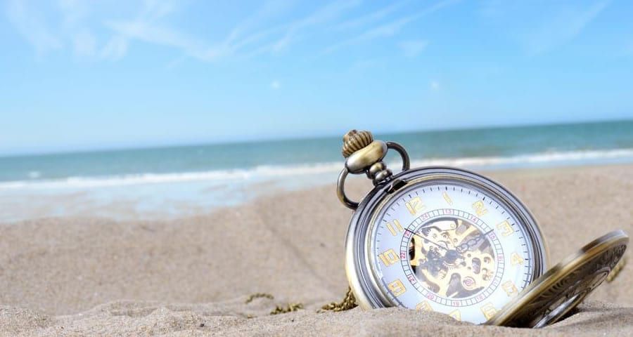 férias vencidas - relógio enterrado na areia da praia.