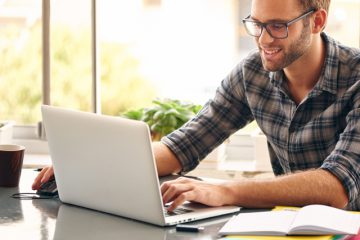 Registro da Empregada Doméstica - homem sorrindo e mexendo no notebook