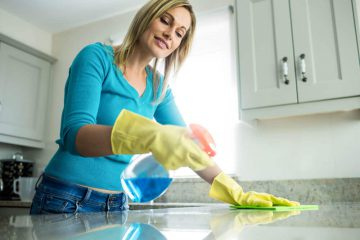 Empregada Doméstica e Cuidadora - mulher com luvas de borracha limpando a pia da cozinha