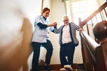 Habilidades de um cuidador de idosos - cuidadora ajudando uma idosa a descer as escadas