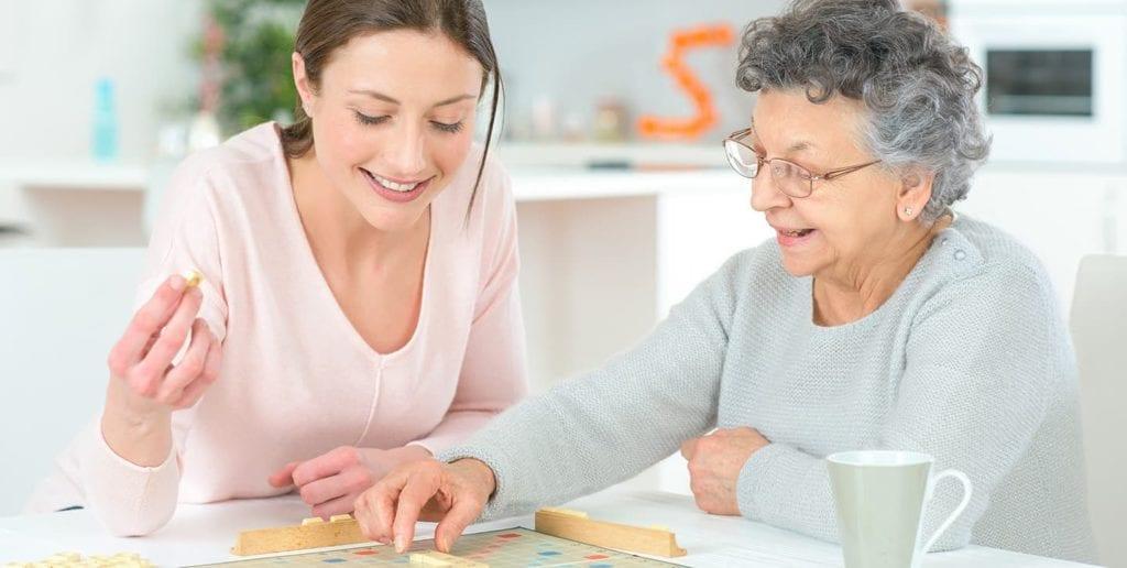 Habilidades de um cuidador de idosos - cuidadora jogando palavras cruzadas com idosa