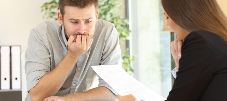 Obrigações do Empregador Doméstico - homem apreensivo olhando um documento
