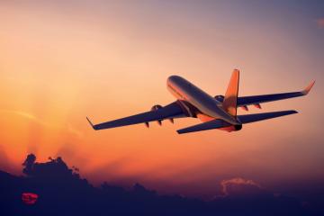Avião voando no horizonte no por do sol