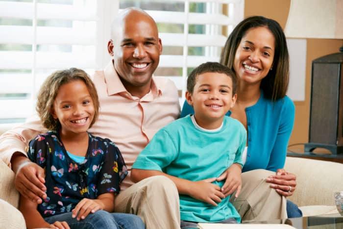 salário família - família feliz e sorridente sentada no sofá